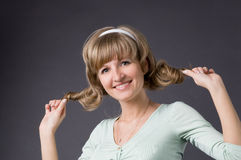 To tighten up hair. The girl tightens up hair in studio on a grey background Royalty Free Stock Image