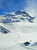 To the top. An off-piste skier climbing a mountain to reach the top where he will hit virgin powder slopes Stock Photo
