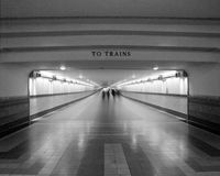 To Trains. Black and White tunnel leading to trains with people Stock Photography