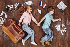To travel is to live. Children lying near travel items. Girl with suitcase royalty free stock image