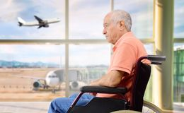 To travel in a wheelchair. Patient senior on a wheelchair at a airport looking outside stock photography