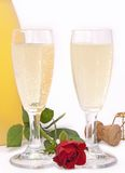 To uncork a bottle of champagne. Two flutes es of champagne with a rose to celebrate a special event Royalty Free Stock Photo