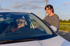To women chatting on a rural road. One standing outside in the glowing evening light and a female driver sitting in her car stock photography