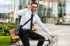 To work on wheels. Side view of smiling young businessman looking at camera and adjusting eyewear while riding on his bicycle Stock Photos