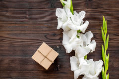 To wrap a gift. Box in kraft paper near flower gladiolus on dark wooden table top view copyspace Royalty Free Stock Photos