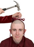 To the young man hammer a bow to a head. The female hand from hammers in a nail into a man head Stock Photo