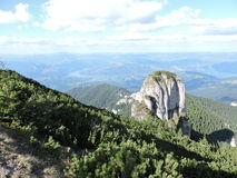 From Toaca Peak, Ceahlau. Imposing rock Panaghia, a sunny landscape Royalty Free Stock Photo