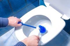 Toalete da limpeza do homem usando o líquido de limpeza da escova e do líquido Imagens de Stock Royalty Free