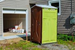Toalete portátil em uma estrutura nova perto da casa nova sob a construção Imagens de Stock Royalty Free