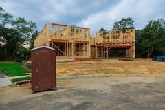 Toalete portátil em uma estrutura nova perto da casa nova sob a construção Fotos de Stock Royalty Free