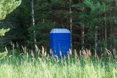Toalete químico exterior azul nas madeiras no verão imagem de stock