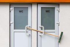 Toalettdörrar stängs med en kvast Den offentliga toaletten arbetar inte arkivfoton