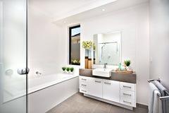Toaletten med ett bad badar bredvid ett fönster och ett klapp Royaltyfri Fotografi