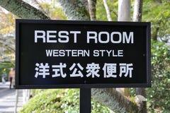 Toaletten undertecknar in japanskt och engelskt språk royaltyfri bild