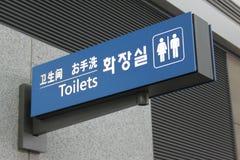 Toaletten undertecknar in kines, japan, korean och engelska Royaltyfria Foton