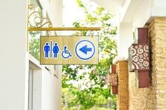 Toaletten undertecknar och riktningen Arkivbild