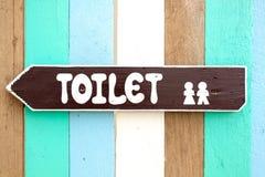 Toaletten undertecknar på den gammala wood väggbakgrunden Royaltyfri Fotografi