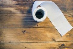Toalettpapper på wood bakgrund Arkivfoton