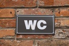 ToalettWC-tecken på den gamla väggen för röd tegelsten Vitt WC-tecken på den svarta metallplattan utomhus- tecken Royaltyfri Fotografi