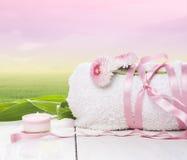 a toalha, amarrada com a fita cor-de-rosa com margarida floresce o fundo da manhã do verão Foto de Stock