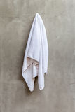 A toalha branca está pendurando no muro de cimento exposto no bathr foto de stock