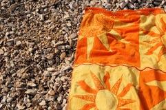 Toalha de banho ensolarada no cascalho   Fotos de Stock Royalty Free
