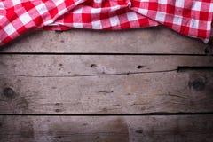 Toalha de cozinha quadriculado vermelha no fundo de madeira do vintage Imagens de Stock