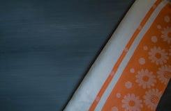 Toalha de mesa alaranjada na opinião preta de madeira da tabela da parte superior Imagens de Stock