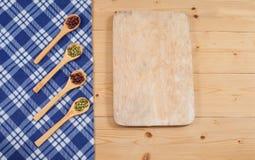 Toalha de mesa, colher de madeira, cutboard na madeira Imagem de Stock