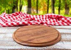 Toalha de mesa quadriculado da mesa da pizza em uma tabela de madeira no fundo borrado da floresta imagens de stock royalty free