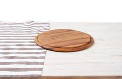 Toalha de mesa vazia na placa de corte de madeira da tabela e da pizza isolada no fundo branco Foco seletivo lugar para o aliment imagens de stock