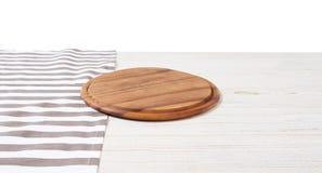 Toalha de mesa vazia na placa de corte de madeira da tabela e da pizza isolada no fundo branco Foco seletivo lugar para o aliment imagem de stock