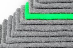 Toalha de terry verde-clara na pilha de outras cinzentas Contraste da cor imagens de stock