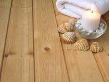 Toalha, shell e vela ardente Fotos de Stock