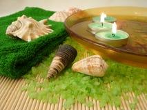 Toalha verde, escudos, velas na placa com água e sal em um s fotografia de stock