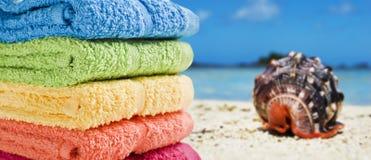 Toalhas coloridas em uma praia branca com um escudo do mar Imagem de Stock Royalty Free