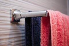 toalhas coloridas que penduram na cremalheira no banheiro, azul e cor-de-rosa, pares, conceito de família imagem de stock