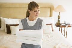Toalhas da terra arrendada da empregada doméstica no sorriso do quarto de hotel Fotografia de Stock Royalty Free