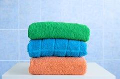 Toalhas de Terry em um nightstand branco no banheiro Telha do azul do fundo foto de stock royalty free