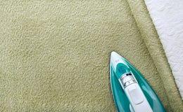 Toalhas de terry modernas e ferro brancos e verde-oliva, vista superior Conceito de Minimalistic da casa, limpeza, passando imagens de stock