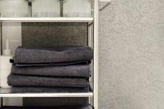 Toalhas, deslizadores de tapete e roupões dobrados em uma prateleira de um armário em um hotel fotos de stock