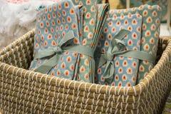 Toalhas do presente com um teste padrão de ponto, amarrado com trança em uma cesta de vime foto de stock royalty free