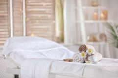 Toalhas e velas na tabela da massagem no salão de beleza dos termas Lugar para o abrandamento imagens de stock