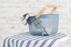 Toalhas na cesta e pinos no fundo claro Fotografia de Stock Royalty Free