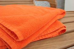 Toalla anaranjada puesta en la madera c Imágenes de archivo libres de regalías