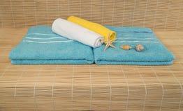 Toalla blanca amarilla azul con las conchas marinas en la estera de bambú Fotos de archivo libres de regalías