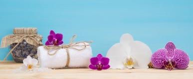 Toalla blanca con el olor de orquídeas en la tabla fotos de archivo libres de regalías