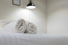 Toalla blanca en cama en el cuarto de invitados para el cliente del hotel Imágenes de archivo libres de regalías