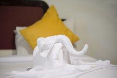 Toalla blanca en forma del elefante en la cama blanca en hotel Fotografía de archivo libre de regalías