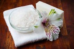 Toalla blanca, sal aromática y flor Imagen de archivo